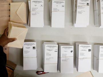 Una persona coloca en la mesa de un colegio electoral las papeletas con las diferentes opciones políticas