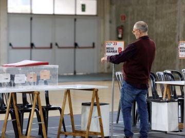 Un funcionario coloca la identificación de una mesa en un colegio electoral de Vitoria