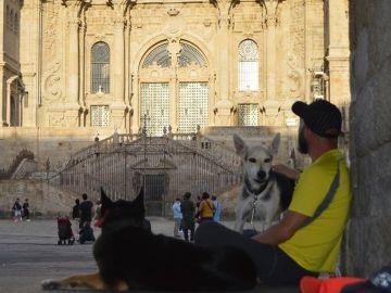 Un hombre con dos perros frente a la catedral de Santiago