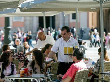 Un camarero sirve bebidas en una terraza en la plaza de la Virgen de Valencia