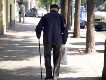Un jubilado camina en una calle.