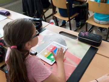 Una niña usando un iPad en clase (Archivo)