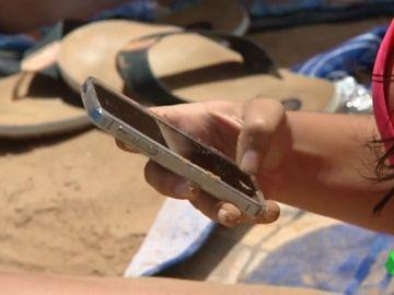 Una persona con un teléfono móvil en la playa.