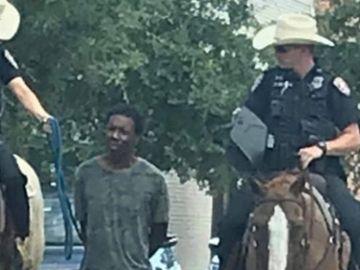 Dos policías transportan a un hombre negro atado con una cuerda.