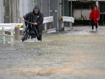 Imagen de un hombre circulando por una calle inundada.