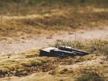 Revólver tirado en el suelo