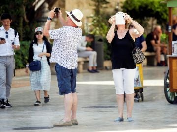 Varios turistas toman fotografías con sus teléfonos