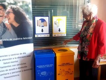 Una mujer recicla una botella de plástico en el contenedor de envases que tienen en la Residencia Stella Maris.