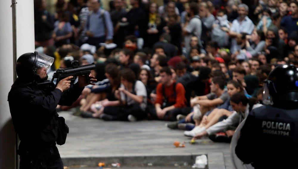Policías antidisturbios ante los manifestantes que se concentraron en el aeropuerto del Prat de Barcelona