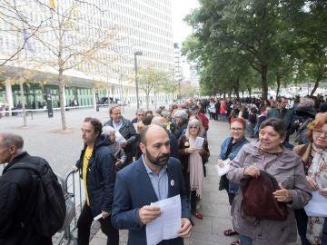 El vicepresidente de Ómnium Cultural, Marcel Mauri (c), acompañado por la activista social, Gabriela Serra (d), esperan frente a la Ciudad de la Justicia, para entregar la documentación de autoinculpación en el marco de una campaña impulsada por la entidad.