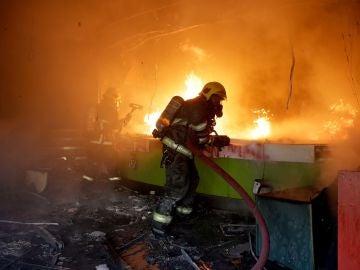 Un bombero trabaja en la extinción de un incendio que se produjo durante una protesta en Chile