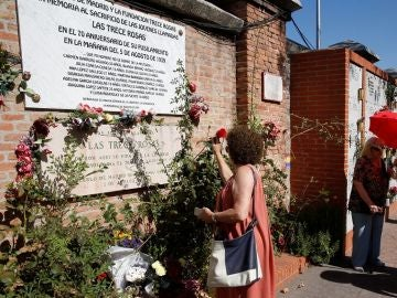 Una mujer coloca una rosa en el muro dedicado a las 'Trece Rosas'