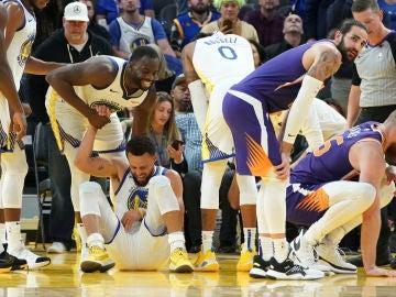 Stephen Curry cae al suelo tras sufrir una grave lesión en su mano izquierda