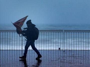 Un hombre pasea por la Playa de la Barceloneta