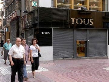 Unos viandantes pasan por delante de una joyería Tous en Lérida