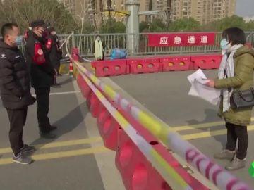 Una madre suplica ayuda en un puesto policial para su hija enferma de leucemia ante el colapso de hospitales en China por el coronavirus