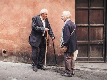 Dos ancianos frente a un domicilio