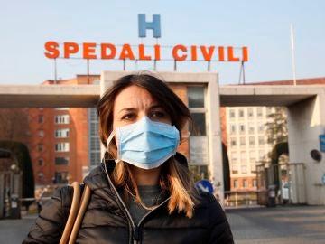 Una mujer con mascarilla en Brescia