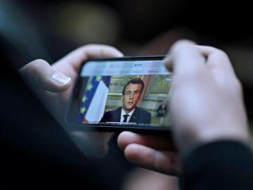 Un ciudadano sigue a través de su móvil el discurso de Emmanuel Macron
