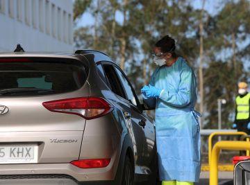Una sanitaria junto a un coche en la crisis por coronavirus