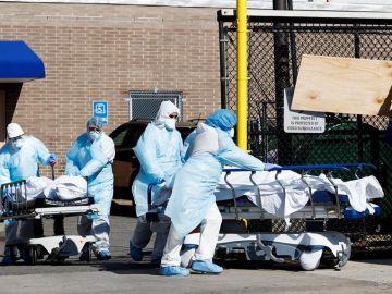Profesionales sanitarios transportan fallecidos por coronavirus en una morgue temporal