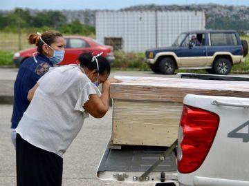 Un familiar de un fallecido llora a las afueras del cementerio