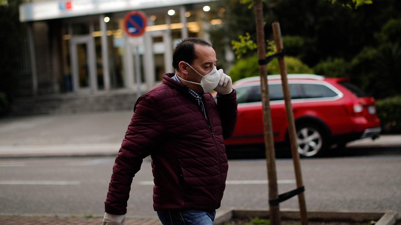 Un hombre con mascarilla pasea por las calles de Madrid