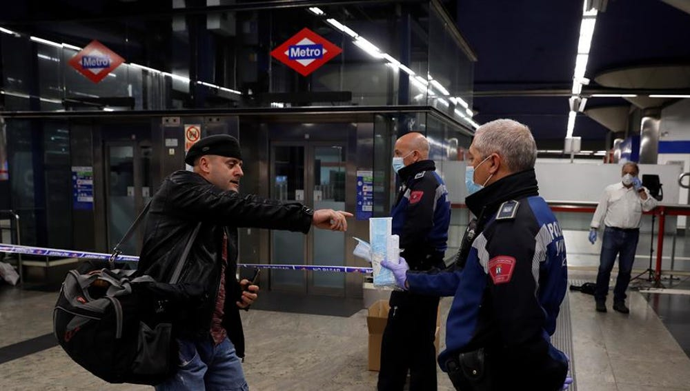 Policías entregan mascarillas en la estación de metro de Nuevos Ministerios en Madrid, este lunes.