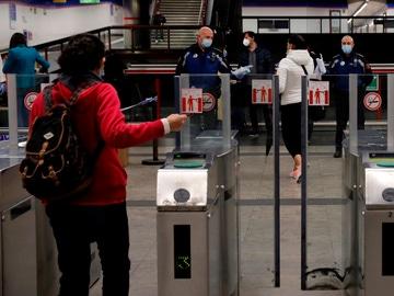 Policías entregan mascarillas en la estación de metro de Nuevos Ministerios en Madrid
