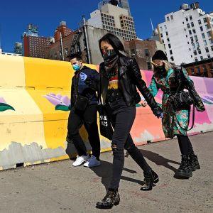 Varias personas caminan por las calles de Nueva York cubriéndose la cara