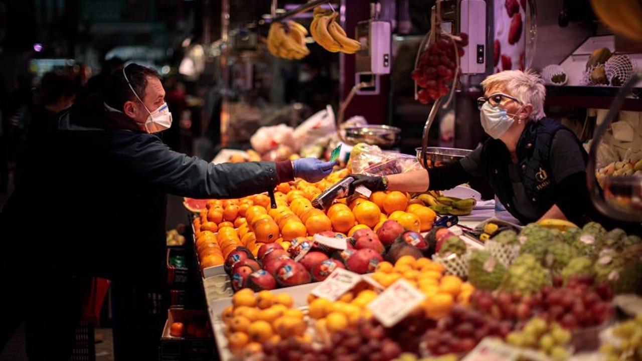 Una persona compra en un puesto de frutas del Mercado Central de Valencia