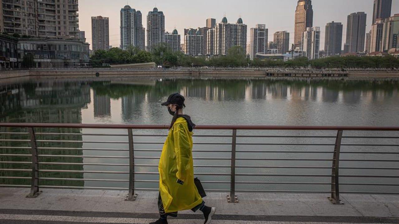 Una mujer camina junto a un lago de Wuhan (China)