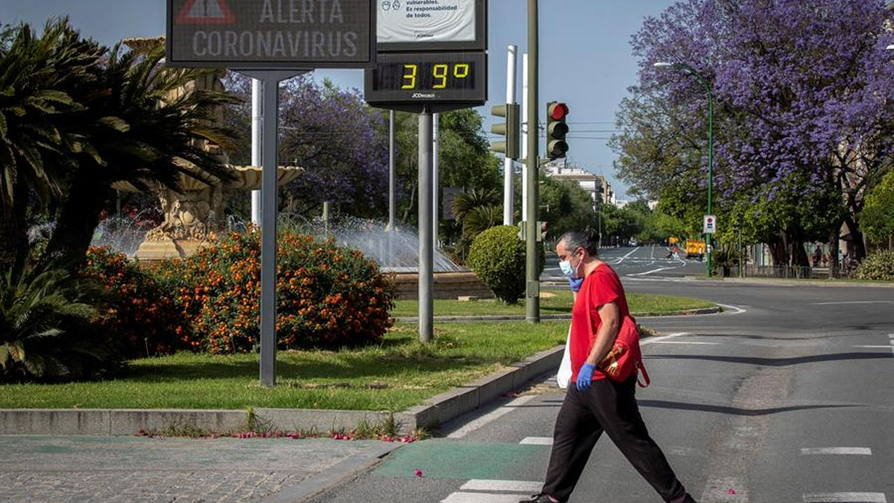 Un hombre protegido con guantes y mascarilla pasea por Sevilla bajo temperaturas de 39ºC