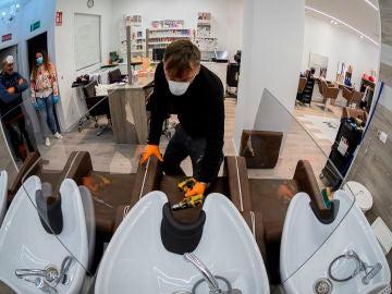 Imagen tomada con una lente ojo de pez de un obrero mientras instala mamparas de separación entre las pilas para lavar cabezas en una peluquería de Alcalá de Henares, Madrid