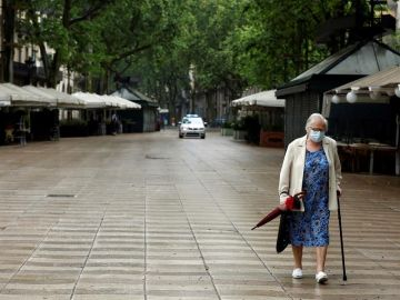 Una mujer protegida con mascarilla pasea por las Ramblas