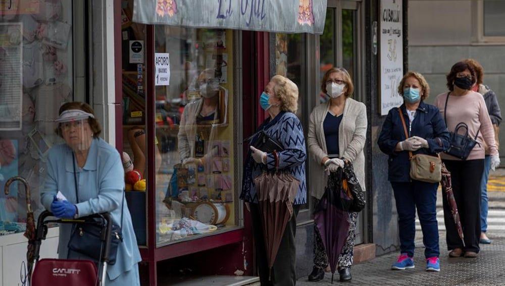 Varias mujeres con mascarillas hacen cola ante una mercería
