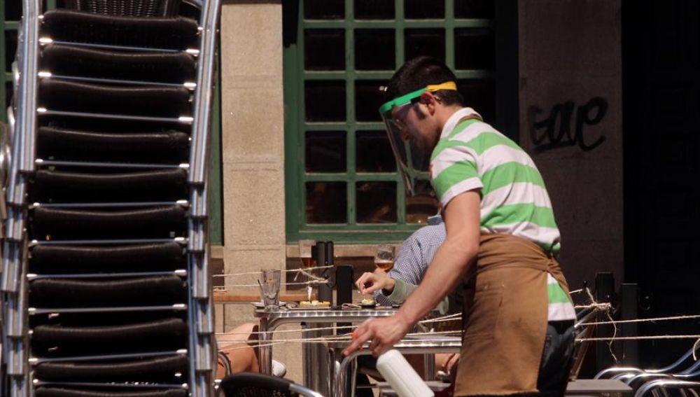 Un trabajador con pantalla protectora desinfecta una terraza en el primer día de la fase 1 en Ponferrada