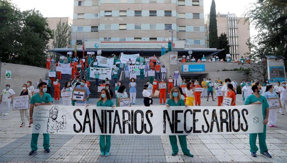 """Miembros del personal sanitario del Hospital Gregorio Marañón posan con una pancarta en la que se lee """"Sanitarios necesarios"""" durante una concentración"""
