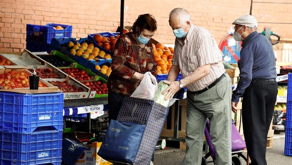 Varias personas hacen sus compras en un mercadillo en Madrid