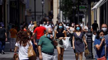 Gente protegida con mascarilla pasea por las calles