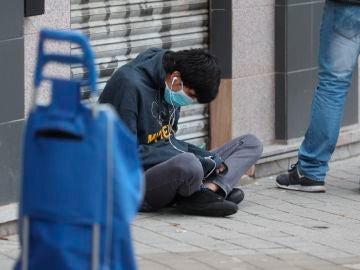 Una persona espera en la fila para recoger alimentos proporcionados por la Asociación de vecinos de Aluche, en Madrid