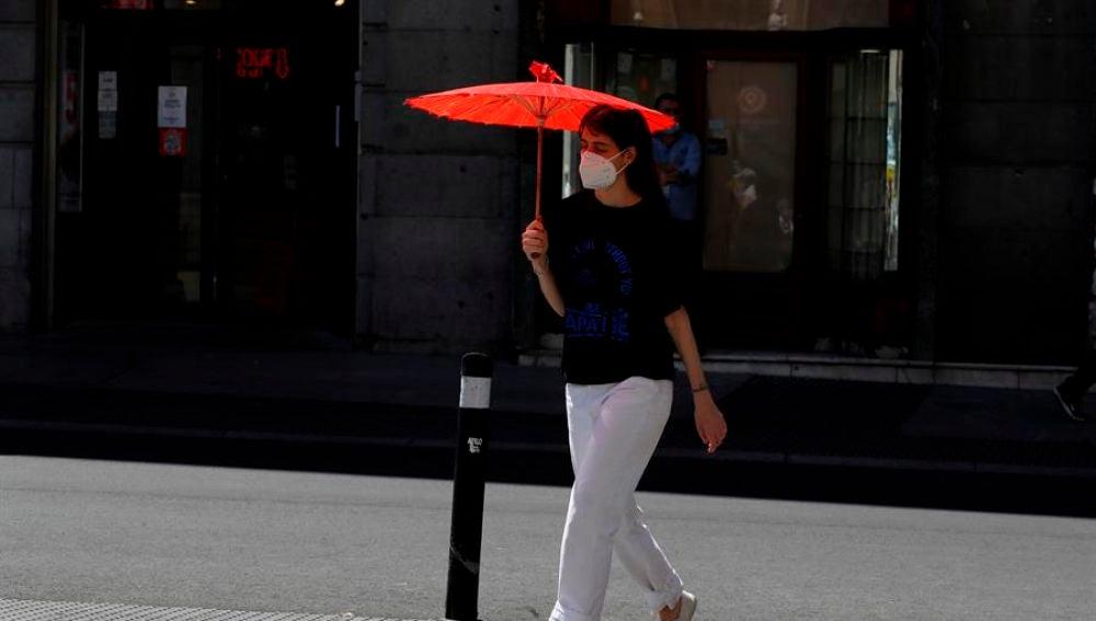 Una mujer se protege del sol con una sombrilla en el centro de Madrid.