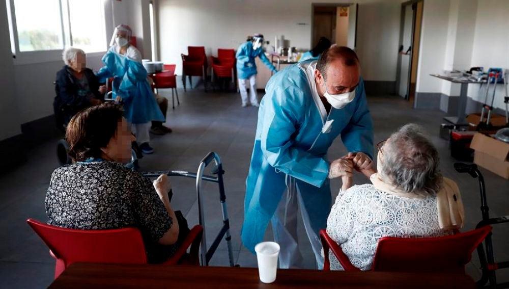 Un sanitario atiende a los ancianos alojados en una residencia