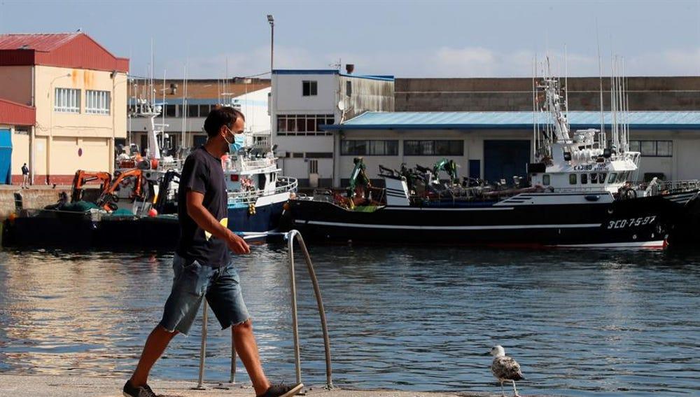 Un trabajador camina por el puerto de Burela, el municipio de A Mariña con más afectados por el brote de coronavirus.