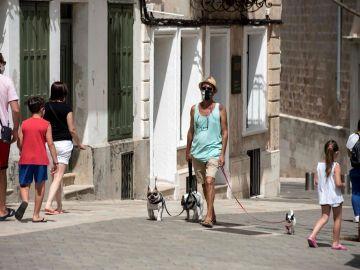 Varias personas caminan por las calles de Mahón (Menorca, España)