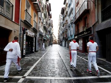 Tres corredores habituales del encierro caminan por una vacía calle Estafeta