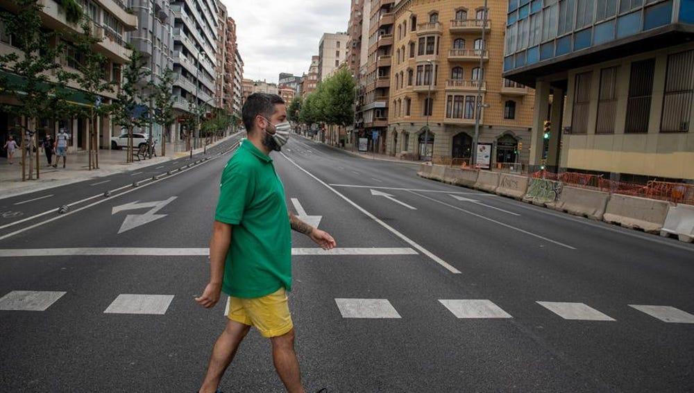Un vecino cruza la calle en una avenida prácticamente vacía en Lleida