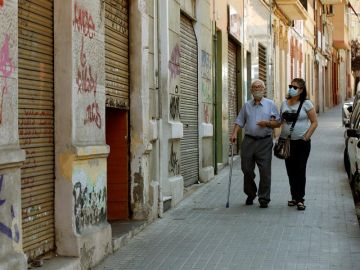 Una mujer acompaña a su padre por una calle de L'Hospitalet