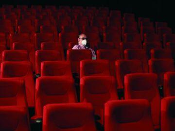 Un espectador espera el comienzo de la película en una sala de cine casi vacía