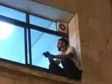 El joven palestino subido a la ventana del hospital para despedirse de su madre tras el cristal